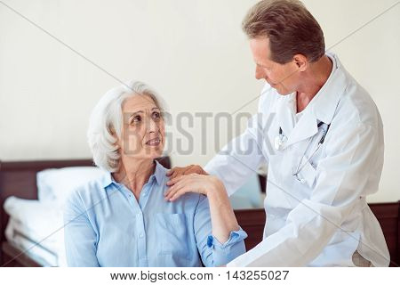 Senior patient. Smiling old woman and doctor speaking with her in clinic