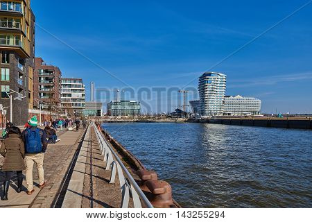 HAMBURG, GERMANY - MARCH 26, 2016: Tourists and visitors stroll along the Elbe quai of the new harbor city of Hamburg and enjoy the warm and sunny weather.