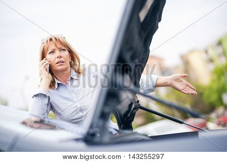 Woman with car trouble in the middle of the street after car breakdown. She is on the phone calling for assistance.She is waiting for the technician to arrive.
