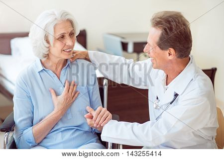 Helpful specialist. Positive senior woman and doctor talking with her and embracing