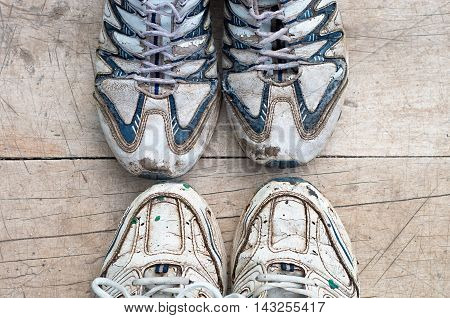 two pairs of worn running shoe on a wooden background