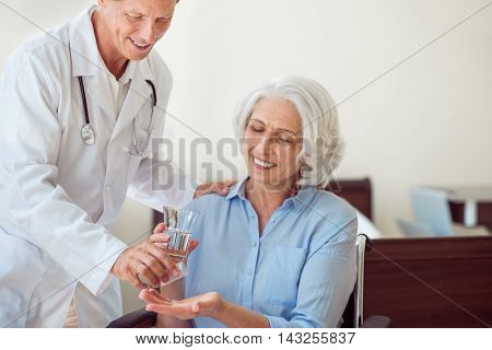 Health care. Cropped image of merry senior woman taking pills and drinking water and cheerful doctor giving her these pills