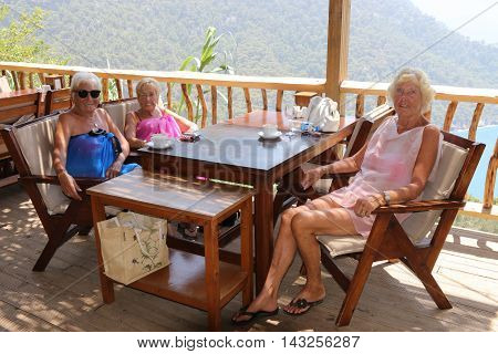 29TH JULY 2016, KABAK,TURKEY: Three old aged pensioners sitting at a table and relaxing with a drink while on vacation in Kabak, Turkey, 29th july 2016