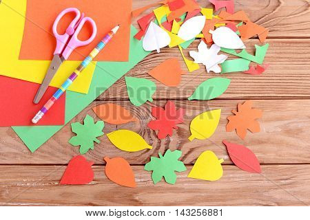 Colored paper sheets, scissors, pencil, autumn colored paper leaves on wooden background. Cutting with scissors. Development of skill for a toddler or preschooler. Top view