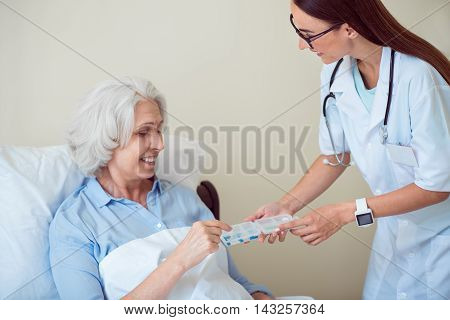 Medical help. Merry senior woman lying in bed and young female doctor giving her pills
