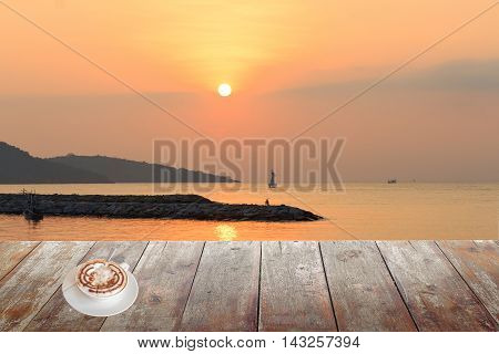 coffee cappuccino on wood table in morning sunrise at sea and space for text may be used as background