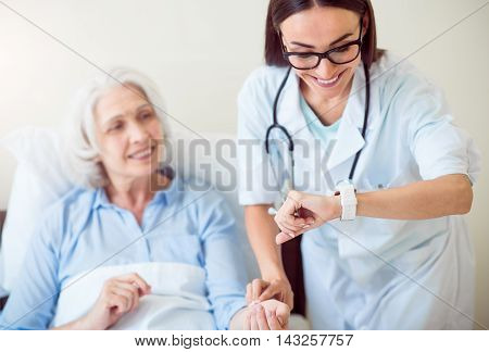 Professional help. Smiling and cheerful old woman lying in bed and young doctor checking her pulse