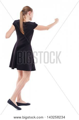 skinny woman funny fights waving his arms and legs. Isolated over white background. Blonde in a short black dress boxing