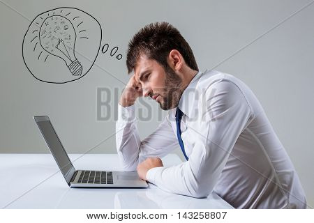 tired young man looking at laptop. It uses a computer while sitting at a table. Office clothing