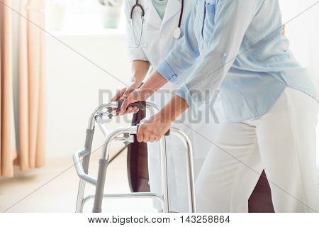 Kind doctor. Cropped image of doctor helping old woman with walking frame