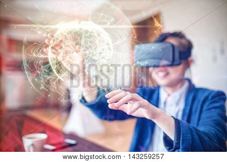 Global technology background in green against young woman using virtual reality glasses