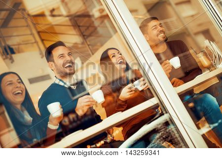 Friends smiling and sitting in a cafehaving a great time.