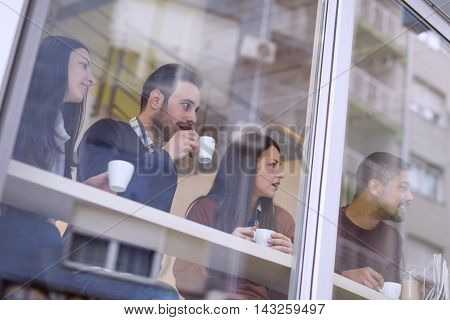 Shot of a friends having a great time in cafe.Friends smiling and sitting in a cafe drinking coffee and enjoying together.