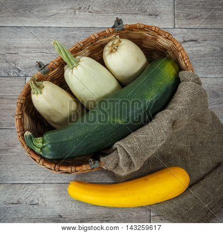 Fresh zucchini or marrow squash or courgette in basket on burlap against wooden background. Vegetables in different shapes and colors concept of diversity top view