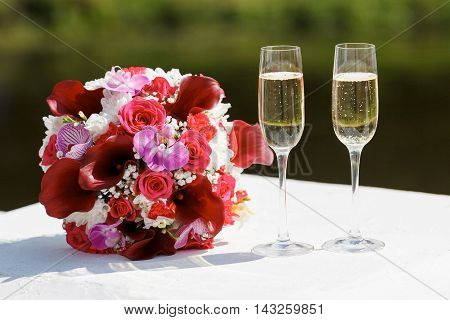 two glasses of sparkling wine and bride's bouquet of red Calla lilies roses carnations and orchids