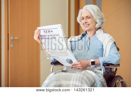 Stay up to date. Smiling and content senior patient sitting in wheelchair and reading newspaper