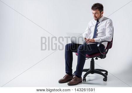 emotional young guy in office clothes working on a laptop computer and sitting on a chair