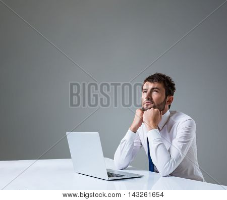 young man thinking uses a laptop computer while sitting at a table. Office clothing. copyspace