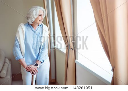 Modern grandmother. Positive and content senior woman standing with crutch being indoors