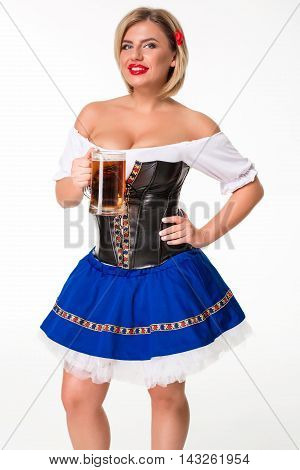 Beautiful young blond girl in dirndl drinks out of oktoberfest beer stein. on white background.