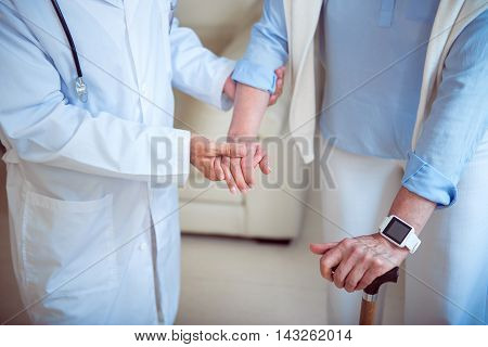 Elderly. Cropped picture of doctor helping and supporting cheerful and content senior patient