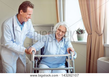 Rehabilitation therapy. Positive doctor helping and supporting delighted senior patient in wheelchair with walking frame