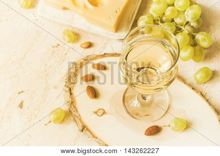Glass of white wine and grapes copy space tinted.