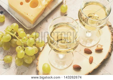 Glasses of white wine and grapes and nuts tinted.