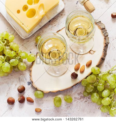 Glasses of white wine grapes and cheese on white background.