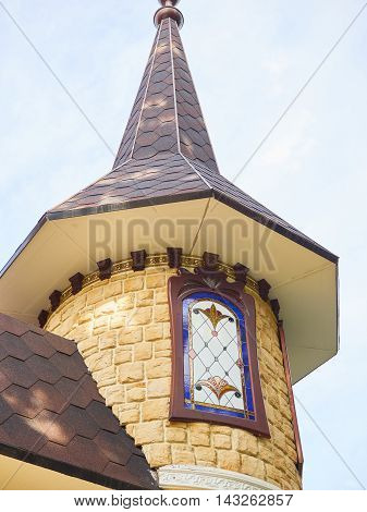 Tower with a spire stone castle closeup on blue sky background. Mosaic on the window glass.