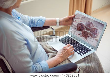 Digital granny. Cropped picture of senior woman in wheelchair searching information in internet with help of laptop