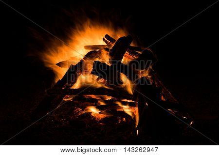 firewood in the bonfire with fire and sparks - background