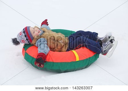 Little handsome boy with skates lies on bright snow tube at winter day