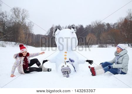Upside down snowman with hat and two happy women sits at winter day