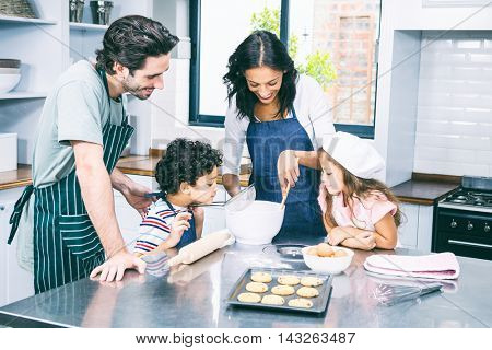 Happy family cooking biscuits together in kitchen at home
