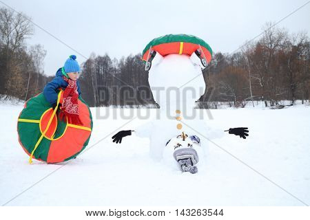 Happy boy with tube stands near upside down snowman at winter day