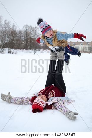 Woman lies on her back and holds handsome little boy on feet in snow