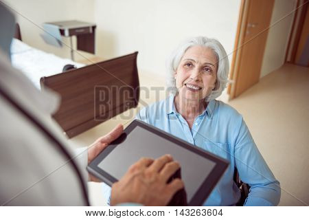 Best clinic. Cropped image of senior happy and smiling woman in wheelchair and doctor holding digital tablet