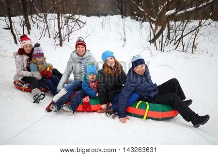 Six people on snow tubes down hill at winter day, focus on father and girl teenager