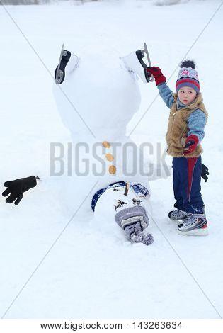 Little handsome boy stands near upside down snowman at winter day