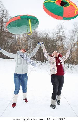 Two happy women throw up bright snow tubes outdoor at winter day