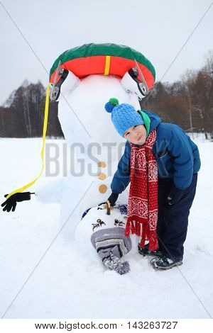Little boy stands near upside down snowman at winter day