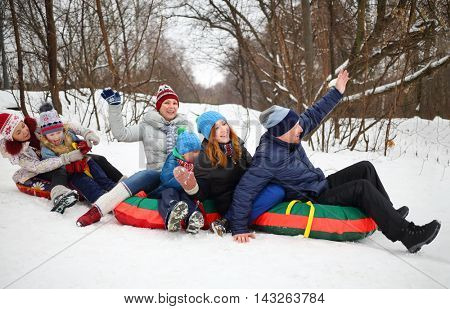 Six people on snow tubes down hill at winter. focus on man and girl teenager
