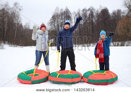 Mother, father and son with snow tubes wave hands in winter day, focus on man