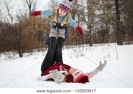 Woman lies on her back and holds little cute boy on feet in snow