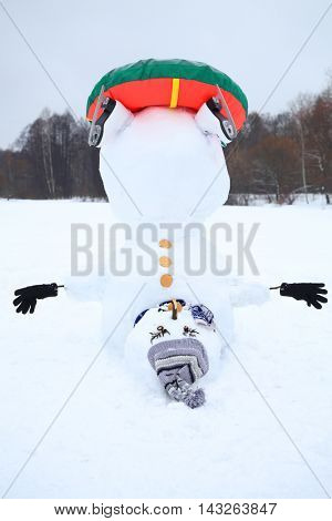 Upside down snowman with hat, snowtube and skates at winter day