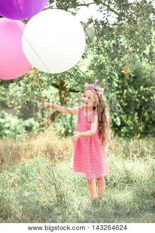 Cute kid girl 5-6 year old wearing summer pink dress holding colorful balloons outdoors. Childhood.