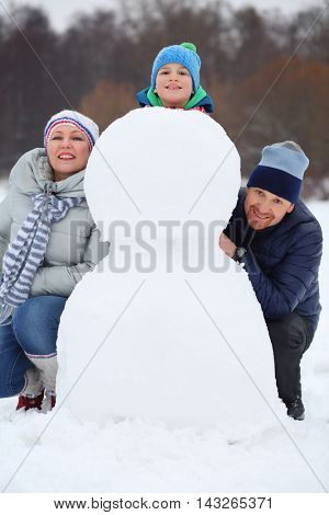 Happy mother, father and son play with snowman at winter day