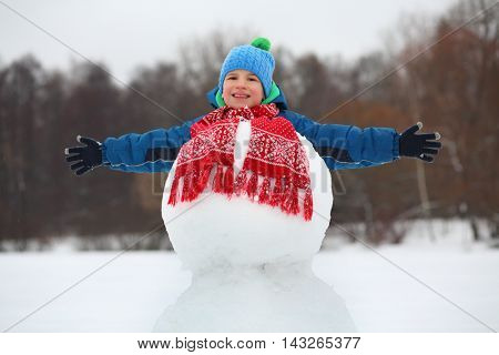 Happy boy in hat plays with snowman - with red scarf at winter day