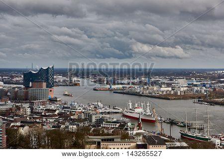 HAMBURG, GERMANY - MARCH 27, 2016: Scenic panorama over Landungsbruecken, New Elbphilharmonie, river Elbe, and docks in Hamburg -